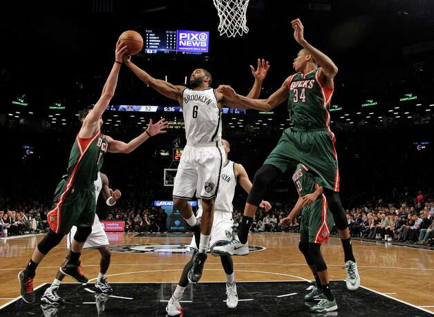 Milwaukee Bucks forward Ersan Ilyasova (7) gets a hand on the ball held by Brooklyn Nets guard Alan Anderson (6) with Bucks guard Giannis Antetokounmpo (34) defending during the first half of an NBA basketball game Wednesday, Nov. 19, 2014, in New York. (AP Photo/Kathy Willens) ORG XMIT: NYKW112 Photo: Kathy Willens / AP
