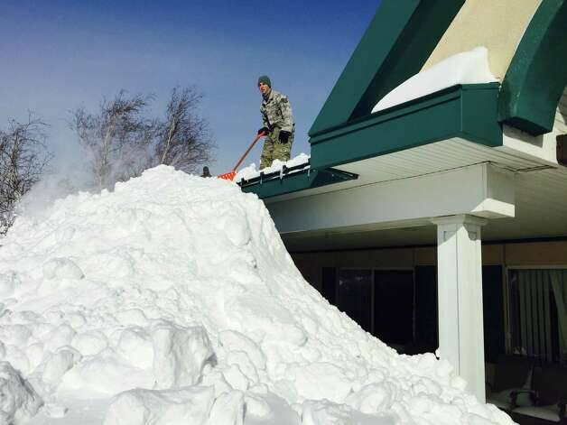 In this photo taken on Wednesday, Nov. 19, 2014, and released by the New York National Guard, an airman with the New York Air National Guard shovels snow off the roof of the Eden Heights Assisted Living Facility in West Seneca, N.Y.  A new blast of lake-effect snow pounded Buffalo for a third day piling more misery on a city already buried by an epic, deadly snowfall that could leave some areas with nearly 8 feet of snow on the ground when it's all done. (AP Photo/New York National Guard, Maj. Mark Frank) ORG XMIT: NY122 Photo: Maj. Mark Frank, AP / NEW YORK NATIONAL GUARD