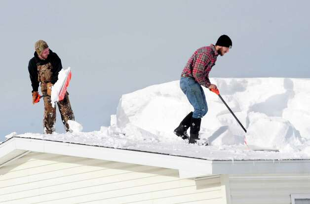 D.J. Schloss, left, and Doug Metz, right shovel off a roof on Abbey Lane in Alden, N.Y. Thursday, Nov. 20, 2014. The weight of the snow has caused problems around the area with roofs collapsing and buildings compromised . (AP Photo/Gary Wiepert) ORG XMIT: NYGW106 Photo: Gary Wiepert, AP / FR170498 AP