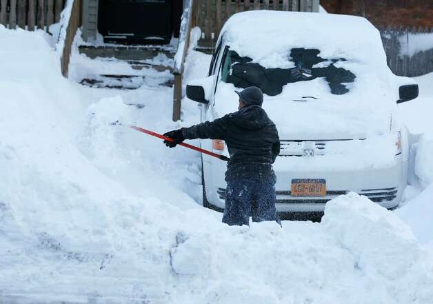 Maria Formholtz shovels her parking area in her south Buffalo neighborhood on Thursday, Nov. 20, 2014, in Buffalo, N.Y.   A new blast of lake-effect snow pounded Buffalo for a third day piling more misery on a city already buried by an epic, deadly snowfall that could leave some areas with nearly 8 feet of snow on the ground when it's all done. (AP Photo/Mike Groll) ORG XMIT: NYMG120 Photo: Mike Groll, AP / AP