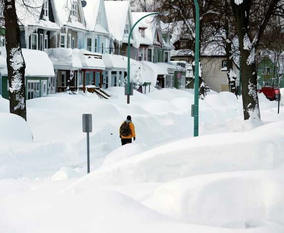 Brian Cintron walks in his snow-bound south Buffalo neighborhood on Thursday, Nov. 20, 2014, in Buffalo, N.Y. A new blast of lake-effect snow pounded Buffalo for a third day piling more misery on a city already buried by an epic, deadly snowfall that could leave some areas with nearly 8 feet of snow on the ground when it's all done. (AP Photo/Mike Groll) ORG XMIT: NYMG111 Photo: Mike Groll, AP / AP