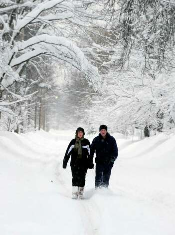 Aileen Pawlowski and Gary Parker walk down Sycamore St. to get essentials from the local store in East Aurora, N.Y. Thursday Nov. 20, 2014. Foot traffic seems to be the best form of transportation after more snow fell last night and driving bans continue across Western New York. (AP Photo/Gary Wiepert) ORG XMIT: NYGW101 Photo: Gary Wiepert, AP / FR170498 AP