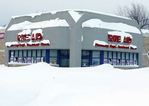 A Rite Aid store is covered in snow in the south Buffalo area on Thursday, Nov. 20, 2014, in Buffalo, N.Y.  A new blast of lake-effect snow pounded Buffalo for a third day piling more misery on a city already buried by an epic, deadly snowfall that could leave some areas with nearly 8 feet of snow on the ground when it's all done. (AP Photo/Mike Groll) ORG XMIT: NYMG119 Photo: Mike Groll, AP / AP