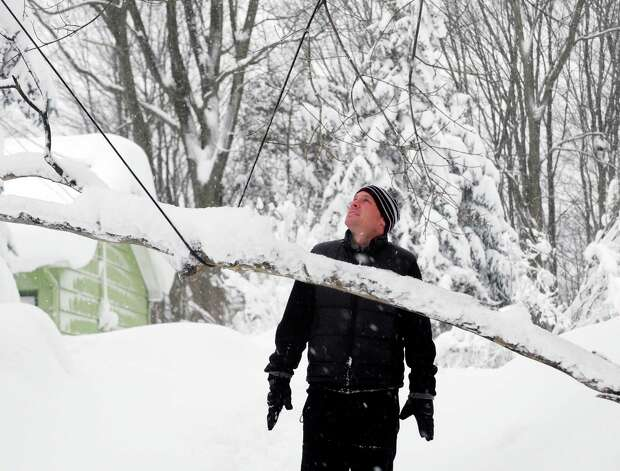 Pete Osmond inspects a branch that fell onto his cable wire on Center Rd. in East Aurora, Thursday, Nov. 20, 2014. A new blast of lake-effect snow pounded Buffalo for a third day piling more misery on a city already buried by an epic, deadly snowfall that could leave some areas with nearly 8 feet of snow on the ground when it's all done. (AP Photo/Gary Wiepert) ORG XMIT: NYGW102 Photo: Gary Wiepert, AP / FR170498 AP