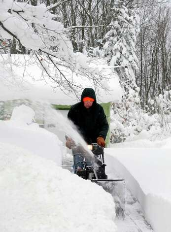 Mike Jason cuts a path with his snowblower after another 15 inches fell last night in East Aurora, N.Y. Thursday, Nov. 20, 2014.  A new blast of lake-effect snow pounded Buffalo for a third day piling more misery on a city already buried by an epic, deadly snowfall that could leave some areas with nearly 8 feet of snow on the ground when it's all done.  (AP Photo/Gary Wiepert) ORG XMIT: NYGW103 Photo: Gary Wiepert, AP / FR170498 AP