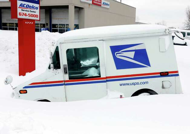 A U.S. Postal vehicle is stuck in snow in a parking lot on Thursday, Nov. 20, 2014, in West Seneca, N.Y.  A new blast of lake-effect snow pounded Buffalo for a third day piling more misery on a city already buried by an epic, deadly snowfall that could leave some areas with nearly 8 feet of snow on the ground when it's all done. (AP Photo/Mike Groll) ORG XMIT: NYMG121 Photo: Mike Groll, AP / AP