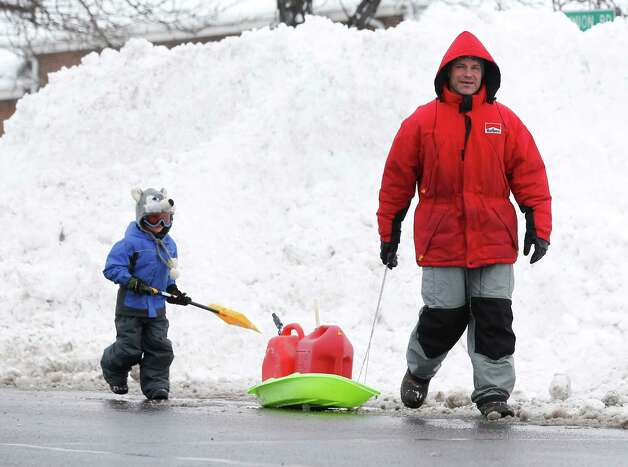 Darrell Felker and son Trevor head to a service station for gasoline to fuel snowblowers on Thursday, Nov. 20, 2014, in West Seneca, N.Y. A new blast of lake-effect snow pounded Buffalo for a third day piling more misery on a city already buried by an epic, deadly snowfall that could leave some areas with nearly 8 feet of snow on the ground when it's all done. (AP Photo/Mike Groll) ORG XMIT: NYMG124 Photo: Mike Groll, AP / AP