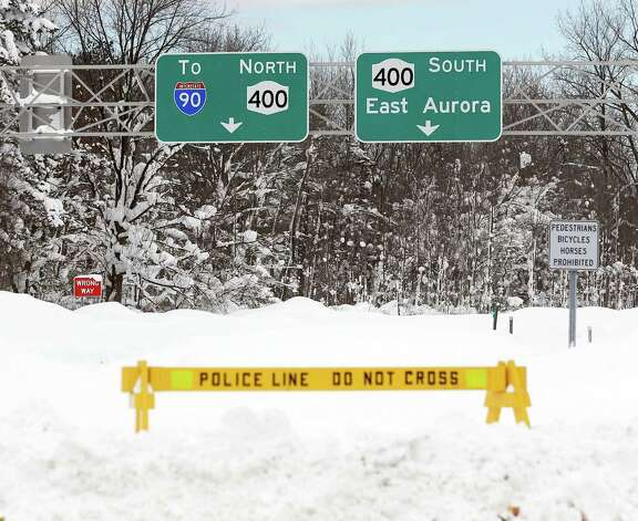 A police barrier prevents vehicles from entering Route 400 on Thursday, Nov. 20, 2014, in West Seneca, N.Y.  A new blast of lake-effect snow pounded Buffalo for a third day piling more misery on a city already buried by an epic, deadly snowfall that could leave some areas with nearly 8 feet of snow on the ground when it's all done. (AP Photo/Mike Groll) ORG XMIT: NYMG123 Photo: Mike Groll, AP / AP