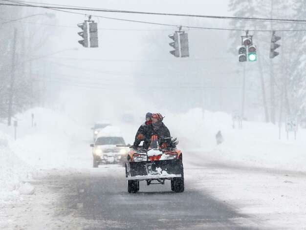 An all terrain vehicle drives along Union Road on Thursday, Nov. 20, 2014, in West Seneca, N.Y. A new blast of lake-effect snow pounded Buffalo for a third day piling more misery on a city already buried by an epic, deadly snowfall that could leave some areas with nearly 8 feet of snow on the ground when it's all done. (AP Photo/Mike Groll) ORG XMIT: NYMG125 Photo: Mike Groll, AP / AP