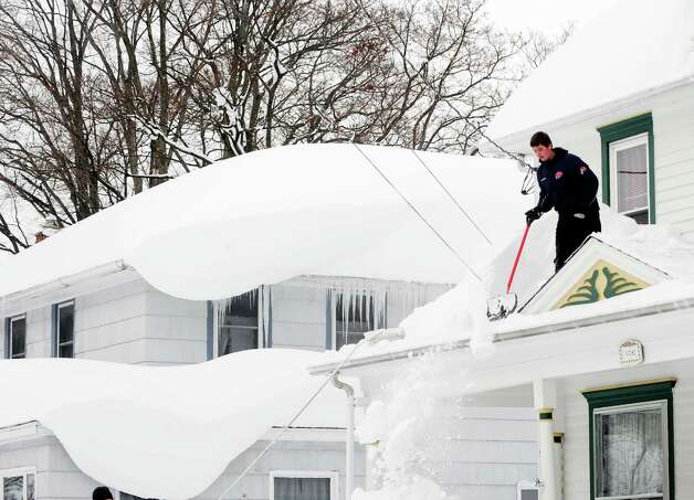 Andrew Zelak cleans the snow from his roof on Irving Place in Alden, N.Y. Thursday, Nov. 20, 2014. A new blast of lake-effect snow roared through western New York with thunder and lightning on Thursday, raising to nearly 6 feet the three-day total in parts of the Buffalo area. The weight of the snow has caused problems around the area with roofs collapsing and structures fracturing. (AP Photo/Gary Wiepert) ORG XMIT: NYGW105 Photo: Gary Wiepert, AP / FR170498 AP