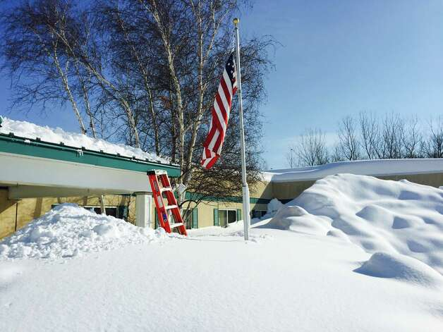 In this photo taken on Wednesday, Nov. 19, 2014, and released by the New York National Guard, snowdrifts nearly reach the roof of the Eden Heights Assisted Living Facility in West Seneca, N.Y.  Airmen with the New York Air National Guard helped shovel snow off the roof of the facility. A new blast of lake-effect snow pounded Buffalo for a third day piling more misery on a city already buried by an epic, deadly snowfall that could leave some areas with nearly 8 feet of snow on the ground when it's all done. (AP Photo/New York National Guard, Maj. Mark Frank) ORG XMIT: NY124 Photo: Maj. Mark Frank, AP / New York National Guard