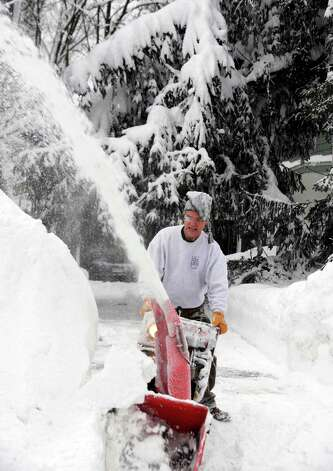 Kurt Almond uses a snowblower to clear his driveway so his wife can attend to her Pharmacy job in East Aurora, , N.Y. Thursday, Nov. 20, 2014.  A new blast of lake-effect snow pounded Buffalo for a third day piling more misery on a city already buried by an epic, deadly snowfall that could leave some areas with nearly 8 feet of snow on the ground when it's all done. (AP Photo/Gary Wiepert) ORG XMIT: NYGW104 Photo: Gary Wiepert, AP / FR170498 AP