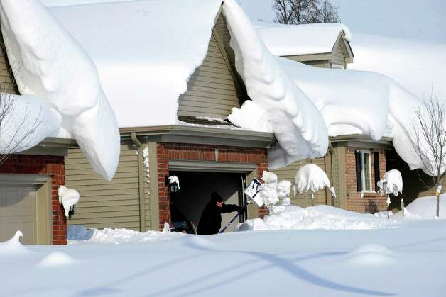 Snowdrifts create a beautiful setting as a man tries to dig out his driveway on Bowen Rd in Lancaster, N.Y. Wednesday, Nov. 19, 2014. A lake-effect snow storm dumped over five feet of snow in areas across Western New York. Another two to three feet of snow is expected in the area, bringing snow totals to over 100 inches, almost a years' worth of snow in three days.  (AP photo/Gary Wiepert) ORG XMIT: NYGW108 Photo: Gary Wiepert, AP / FR170498 AP