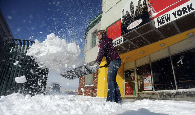 Samantha Freeman shovels snow off the sidewalk in Public Sqaure Wednesday, Nov. 19, 2014  in Watertown, N.Y.  A ferocious lake-effect storm left the Buffalo area buried under 6 feet of snow Wednesday, trapping people on highways and in homes, and another storm expected to drop 2 to 3 feet more was on its way. (AP Photo/The Watertown Daily Times, Justin Sorensen)  SYRACUSE OUT ORG XMIT: NYWAT102 Photo: Justin Sorensen, AP / The Watertown Daily Times