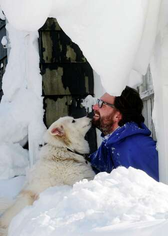Steve Corbett opens his window under snow drifts and greets his neighbor's dog Wednesday, Nov. 19, 2014, on Central Ave in Lancaster, N.Y. A lake-effect snow storm dumped over five feet of snow in areas across Western New York. Another two to three feet of snow is expected s expected in the area, bringing snow totals to over 100 inches, almost a years' worth of snow in three days.  (AP photo/Gary Wiepert) ORG XMIT: NYGW109 Photo: Gary Wiepert, AP / FR170498 AP