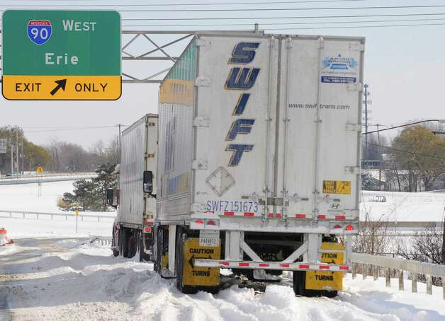 Truckers sit and wait in their tractor trailers for the New York State Thruway to reopen Wednesday, Nov. 19, 2014, at an entrance ramp in Cheektowaga, N.Y.  A lake-effect snow storm dumped over five feet of snow in areas across Western New York. Another two to three feet of snow is expected in the area, bringing snow totals to over 100 inches, almost a years' worth of snow in three days.  (AP Photo/Gary Wiepert) ORG XMIT: NYGW110 Photo: Gary Wiepert, AP / FR170498 AP