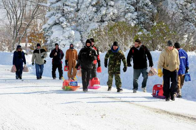 Neighbors band together for a supply run on groceries and gas to help them dig out after a massive snow fall in Lancaster, N.Y. Wednesday, Nov. 19, 2014. Another two to three feet of snow is expected in the area.  (AP Photo/Gary Wiepert) ORG XMIT: NYGW112 Photo: Gary Wiepert, AP / FR170498 AP