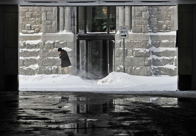 A man talks on the phone while walking on Arcade Street Wednesday, Nov. 19, 2014,  in Watertown, N.Y.  A ferocious lake-effect storm left the Buffalo area buried under 6 feet of snow Wednesday, trapping people on highways and in homes, and another storm expected to drop 2 to 3 feet more was on its way. (AP Photo/The Watertown Daily Times, Justin Sorensen)  SYRACUSE OUT ORG XMIT: NYWAT103 Photo: Justin Sorensen, AP / Watertown Daily Times