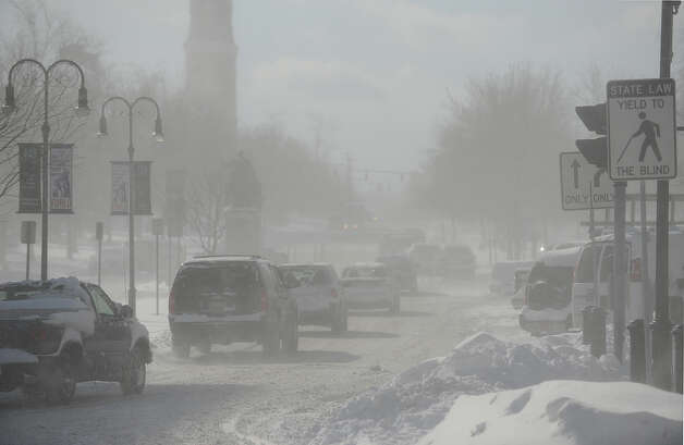 Sun and wind gusts make for limited visibility on Washington Street in Watertown, N.Y., Wednesday, Nov. 19, 2014.  A ferocious lake-effect storm left the Buffalo area buried under 6 feet of snow Wednesday, trapping people on highways and in homes, and another storm expected to drop 2 to 3 feet more was on its way. (AP Photo/The Watertown Daily Times, Justin Sorensen)  SYRACUSE OUT ORG XMIT: NYWAT105 Photo: Justin Sorensen, AP / Watertown Daily Times