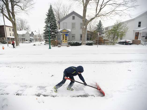 In a Tuesday, Nov. 18, 2014 photo, Nathaniel J. Ford, 11, shovels the sidewalk in front of his house, on William Street in Watertown, N.Y.  Watertown schools were closed Tuesday. A ferocious lake-effect storm left the Buffalo area buried under 6 feet of snow, trapping people on highways and in homes, and another storm expected to drop 2 to 3 feet more was on its way. (AP Photo/The Watertown Daily Times, Justin Sorensen)  SYRACUSE OUT ORG XMIT: NYWAT107 Photo: Justin Sorensen, AP / Watertown Daily Times
