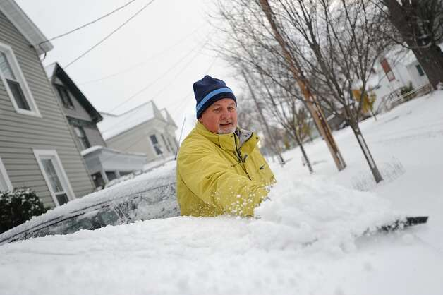 In a Tuesday, Nov. 18, 2014 photo, Brian F. Miller clears snow off his wife's car on Boyd Street in Watertown, N.Y.  Before he finished his wife announced from the porch that she didn't have to go to work at the Jefferson County Courthouse due to weather.   A ferocious lake-effect storm left the Buffalo area buried under 6 feet of snow, trapping people on highways and in homes, and another storm expected to drop 2 to 3 feet more was on its way. (AP Photo/The Watertown Daily Times, Justin Sorensen)  SYRACUSE OUT ORG XMIT: NYWAT108 Photo: Justin Sorensen, AP / Watertown Daily Times