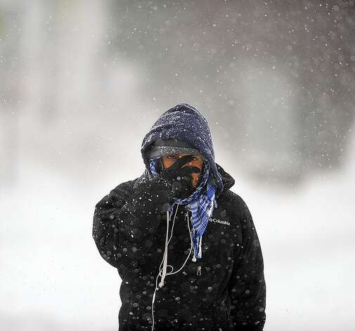 In a Tuesday, Nov. 18, 2014 photo, Joel Sanchez, of Watertown, N.Y., wipes snow from his face while walking down Arsenal Street on his way to help a friend shovel in Watertown.   A ferocious lake-effect storm left the Buffalo area buried under 6 feet of snow, trapping people on highways and in homes, and another storm expected to drop 2 to 3 feet more was on its way. (AP Photo/The Watertown Daily Times, Justin Sorensen)  SYRACUSE OUT ORG XMIT: NYWAT111 Photo: Justin Sorensen, AP / Watertown Daily Times