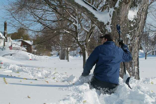 Tom Wilson, 28, of West Seneca, N.Y. , waist high in snow, took advantage of a respite in the snowfall to try to shovel his way down a Buffalo, N.Y., sidewalk, Wednesday, Nov. 19, 2014. He was heading for a friend's house after spending 36 hours at the Consumer Beverages warehouse where he works.  (AP Photo/Carolyn Thompson) ORG XMIT: RPCT201 Photo: Carolyn Thompson, AP / ap