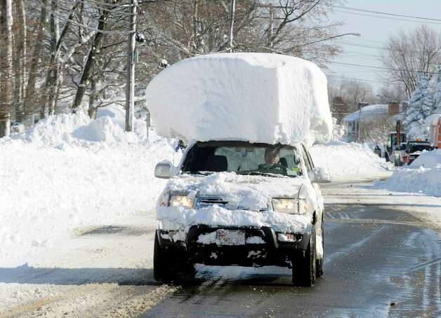 A vehicle, with a large chunk of snow on its top, drives along Route 20 after digging out after a massive snow fall in Lancaster, N.Y. Wednesday, Nov. 19, 2014. Another two to three feet of snow is expected in the area. (AP Photo/Gary Wiepert) ORG XMIT: NYGW113 Photo: Gary Wiepert, AP / FR170498 AP