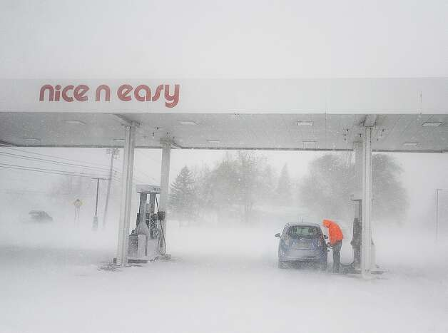 In a Tuesday, Nov. 18, 2014 photo, a man puts gas in his tank as snow falls at a gas station on New York State Route 12F near Brownville, N.Y. A ferocious lake-effect storm left the Buffalo area buried under 6 feet of snow, trapping people on highways and in homes, and another storm expected to drop 2 to 3 feet more was on its way. (AP Photo/The Watertown Daily Times, Justin Sorensen) SYRACUSE OUT ORG XMIT: NYWAT112 Photo: Justin Sorensen, AP / Watertown Daily Times
