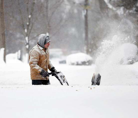 Ken Velie clears snow from his driveway on Wednesday, Nov. 19, 2014, in Lancaster, N.Y. Lake-effect snow pummeled areas around Buffalo for a second straight day, leaving residents stuck in their homes as officials tried to clear massive snow mounds with another storm looming. (AP Photo/Mike Groll) ORG XMIT: NYMG101 Photo: Mike Groll, AP / AP