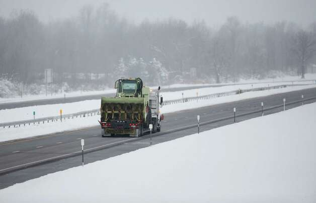 A truck carries a snow clearing vehicle along the New York State Thruway headed for the Buffalo area on Wednesday, Nov. 19, 2014, in Lancaster, N.Y. Lake-effect snow pummeled areas around Buffalo for a second straight day, leaving residents stuck in their homes as officials tried to clear massive snow mounds with another storm looming. A 132-mile stretch of the Thruway in western New York remains closed as as another round of snow is expected overnight and into Thursday. (AP Photo/Mike Groll) ORG XMIT: NYMG102 Photo: Mike Groll, AP / AP