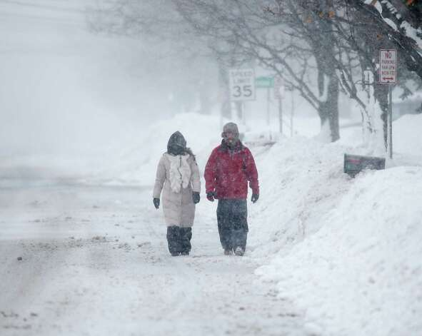 Pedestrians walk along a snow-covered street on Wednesday, Nov. 19, 2014, in Lancaster, N.Y. Lake-effect snow pummeled areas around Buffalo for a second straight day, leaving residents stuck in their homes as officials tried to clear massive snow mounds with another storm looming. (AP Photo/Mike Groll) ORG XMIT: NYMG104 Photo: Mike Groll, AP / AP