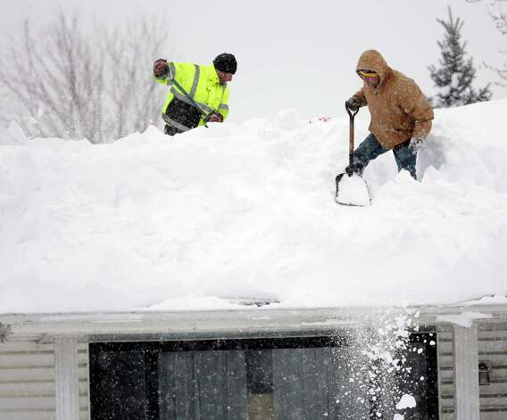 Mark Settlemyer, left, gets help clearing snow from the roof of his mother's house from Ken Wesley on Wednesday, Nov. 19, 2014, in Lancaster, N.Y. Lake-effect snow pummeled areas around Buffalo for a second straight day, leaving residents stuck in their homes as officials tried to clear massive snow mounds with another storm looming. (AP Photo/Mike Groll) ORG XMIT: NYMG108 Photo: Mike Groll, AP / AP