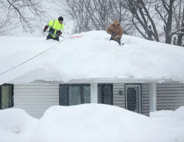 Mark Settlemyer, left, gets help clearing snow from the roof of his mother's house from Ken Wesley on Wednesday, Nov. 19, 2014, in Lancaster, N.Y. Lake-effect snow pummeled areas around Buffalo for a second straight day, leaving residents stuck in their homes as officials tried to clear massive snow mounds with another storm looming. (AP Photo/Mike Groll) ORG XMIT: NYMG107 Photo: Mike Groll, AP / AP