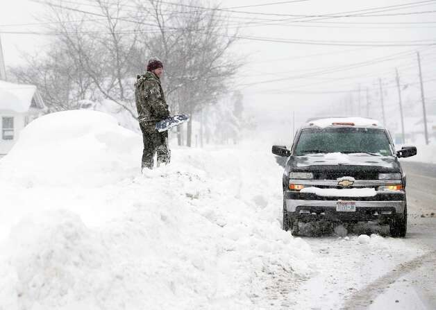 Jeremy Bauer stands on a snowbank next to a buried car outside his brother's house on Wednesday, Nov. 19, 2014, in Lancaster, N.Y. Lake-effect snow pummeled areas around Buffalo for a second straight day, leaving residents stuck in their homes as officials tried to clear massive snow mounds with another storm looming. (AP Photo/Mike Groll) ORG XMIT: NYMG105 Photo: Mike Groll, AP / AP