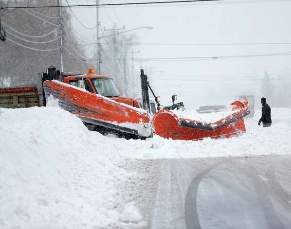 A plow truck clears an opening from a side street on Wednesday, Nov. 19, 2014, in Lancaster, N.Y.  Lake-effect snow pummeled areas around Buffalo for a second straight day, leaving residents stuck in their homes as officials tried to clear massive snow mounds with another storm looming. (AP Photo/Mike Groll) ORG XMIT: NYMG106 Photo: Mike Groll, AP / AP