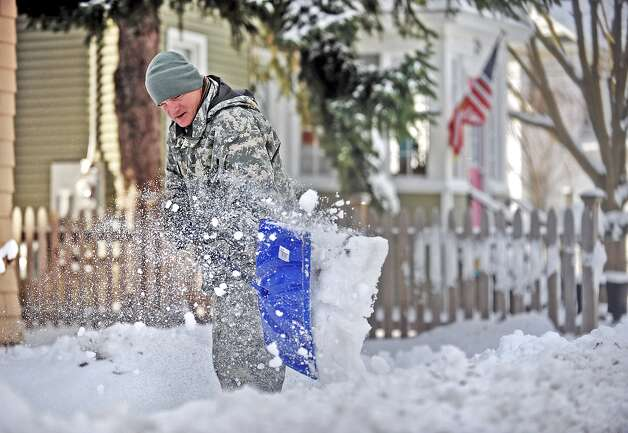 Spc. Cory Amato, from Fort Drumm, shovels snow from the sidewalk outside his house on Franklin Street Wednesday, Nov. 19, 2014, in Watertown, N.Y. (AP Photo/The Watertown Daily Times, Justin Sorensen)  SYRACUSE OUT ORG XMIT: NYWAT201 Photo: Justin Sorensen, AP / The Watertown Daily Times