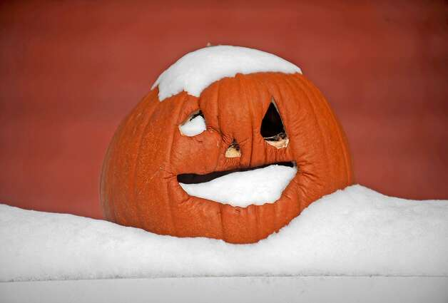 A Jack-o'-lantern sits in the snow at a home on Franklin Street Wednesday, Nov. 19, 2014, in Watertown, N.Y. (AP Photo/The Watertown Daily Times, Justin Sorensen)  SYRACUSE OUT ORG XMIT: NYWAT203 Photo: Justin Sorensen, AP / The Watertown Daily Times