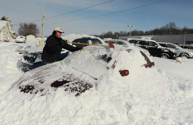Tony K., general sales manager at Toyota of Batavia, clears snow off a buried car on the lot Wednesday morning, Nov. 19, 2014, in Batavia, N.Y. (AP Photo/The Daily News, Mark Gutman) ORG XMIT: NYBAT202 Photo: Mark Gutman, AP / The Daily News