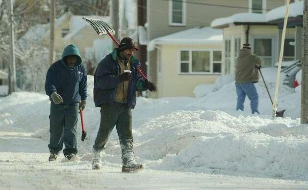 A couple a shovelers walk down North Street looking to remove snow Wednesday, Nov. 19, 2014, in Batavia, N.Y. (AP Photo/The Daily News, Mark Gutman) ORG XMIT: NYBAT203 Photo: Mark Gutman, AP / The Daily News