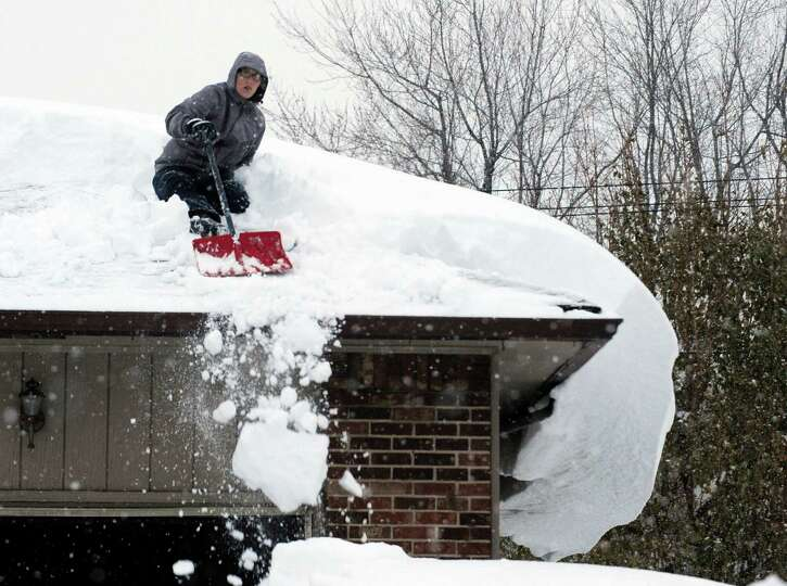A young person sits atop a roof shoveling snowdrifts on French Rd. in Cheektowaga, N.Y. Wednesday, N