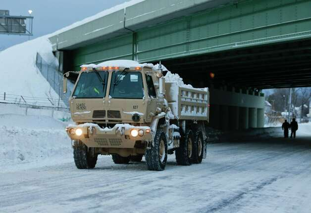 A National Guard vehicle carries snow from a snow-bound neighborhood in south Buffalo  on Thursday, Nov. 20, 2014, in Buffalo, N.Y. A new blast of lake-effect snow pounded Buffalo for a third day piling more misery on a city already buried by an epic, deadly snowfall that could leave some areas with nearly 8 feet of snow on the ground when it's all done. (AP Photo/Mike Groll) ORG XMIT: NYMG103 Photo: Mike Groll, AP / AP