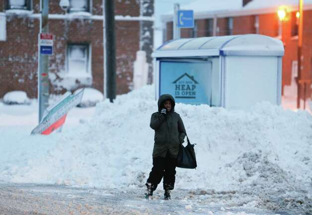 A woman waits for a bus on Thursday, Nov. 20, 2014, in Buffalo, N.Y. A new blast of lake-effect snow pounded Buffalo for a third day piling more misery on a city already buried by an epic, deadly snowfall that could leave some areas with nearly 8 feet of snow on the ground when it's all done. (AP Photo/Mike Groll) ORG XMIT: NYMG101 Photo: Mike Groll, AP / AP