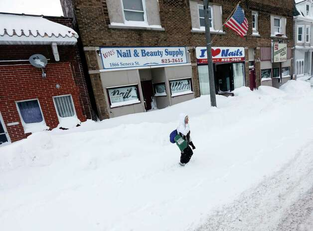 A woman walks along a snow-covered street in the south Buffalo area on Thursday, Nov. 20, 2014, in Buffalo, N.Y. A new blast of lake-effect snow pounded Buffalo for a third day piling more misery on a city already buried by an epic, deadly snowfall that could leave some areas with nearly 8 feet of snow on the ground when it's all done. (AP Photo/Mike Groll) ORG XMIT: NYMG104 Photo: Mike Groll, AP / AP