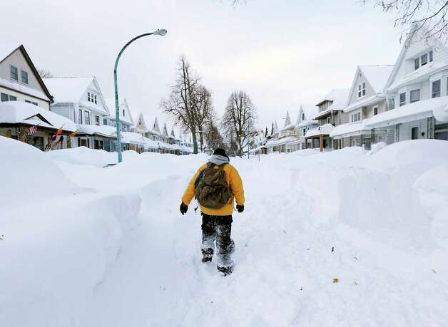 Brian Cintron walks in his snow-bound south Buffalo neighborhood on Thursday, Nov. 20, 2014, in Buffalo, N.Y. A new blast of lake-effect snow pounded Buffalo for a third day piling more misery on a city already buried by an epic, deadly snowfall that could leave some areas with nearly 8 feet of snow on the ground when it's all done. (AP Photo/Mike Groll) ORG XMIT: NYMG107 Photo: Mike Groll, AP / AP