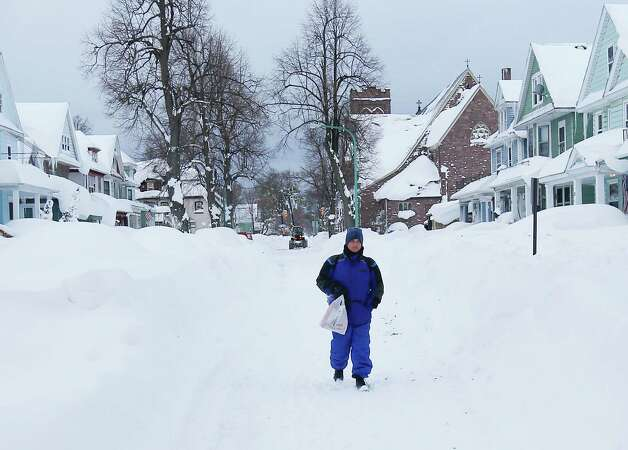 Daryl Brothers walks in his his snow-bound south Buffalo neighborhood on Thursday, Nov. 20, 2014, in Buffalo, N.Y. A new blast of lake-effect snow pounded Buffalo for a third day piling more misery on a city already buried by an epic, deadly snowfall that could leave some areas with nearly 8 feet of snow on the ground when it's all done. (AP Photo/Mike Groll) ORG XMIT: NYMG108 Photo: Mike Groll, AP / AP