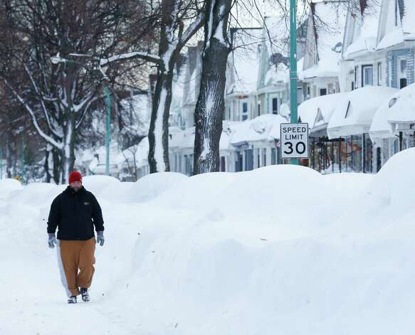 Chris Weiglein walks along his snow-bound south Buffalo neighborhood on Thursday, Nov. 20, 2014, in Buffalo, N.Y. A new blast of lake-effect snow pounded Buffalo for a third day piling more misery on a city already buried by an epic, deadly snowfall that could leave some areas with nearly 8 feet of snow on the ground when it's all done. (AP Photo/Mike Groll) ORG XMIT: NYMG110 Photo: Mike Groll, AP / AP