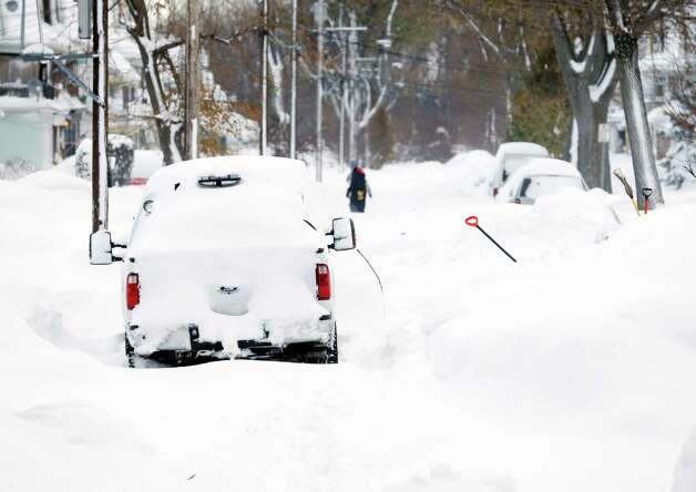A snow-bound truck blocks a street in the south Buffalo area on Thursday, Nov. 20, 2014, in Buffalo, N.Y. A new blast of lake-effect snow pounded Buffalo for a third day piling more misery on a city already buried by an epic, deadly snowfall that could leave some areas with nearly 8 feet of snow on the ground when it's all done. (AP Photo/Mike Groll) ORG XMIT: NYMG109 Photo: Mike Groll, AP / AP