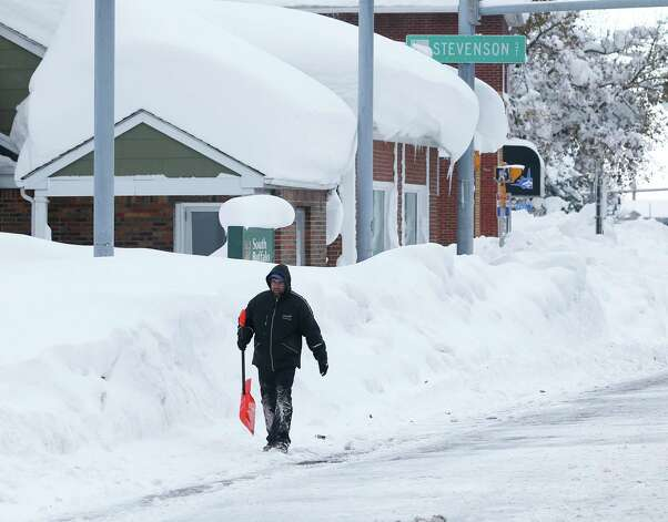 A man carries a shovel as he walks in the south Buffalo area on Thursday, Nov. 20, 2014, in Buffalo, N.Y. A new blast of lake-effect snow pounded Buffalo for a third day piling more misery on a city already buried by an epic, deadly snowfall that could leave some areas with nearly 8 feet of snow on the ground when it's all done. (AP Photo/Mike Groll) ORG XMIT: NYMG113 Photo: Mike Groll, AP / AP