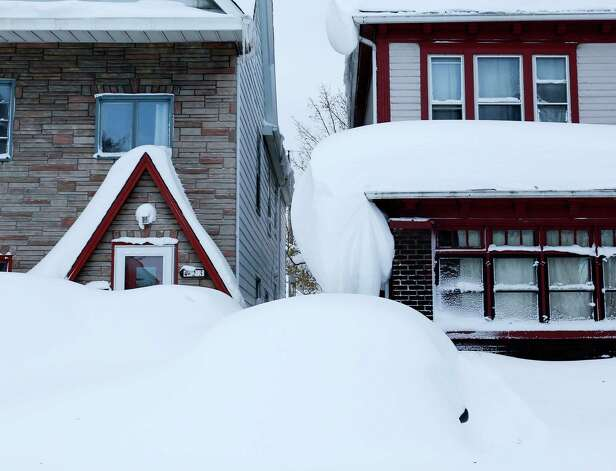 Snow is piled high on a vehicle and on houses in the south Buffalo area on Thursday, Nov. 20, 2014, in Buffalo, N.Y. A new blast of lake-effect snow pounded Buffalo for a third day piling more misery on a city already buried by an epic, deadly snowfall that could leave some areas with nearly 8 feet of snow on the ground when it's all done. (AP Photo/Mike Groll) ORG XMIT: NYMG116 Photo: Mike Groll, AP / AP